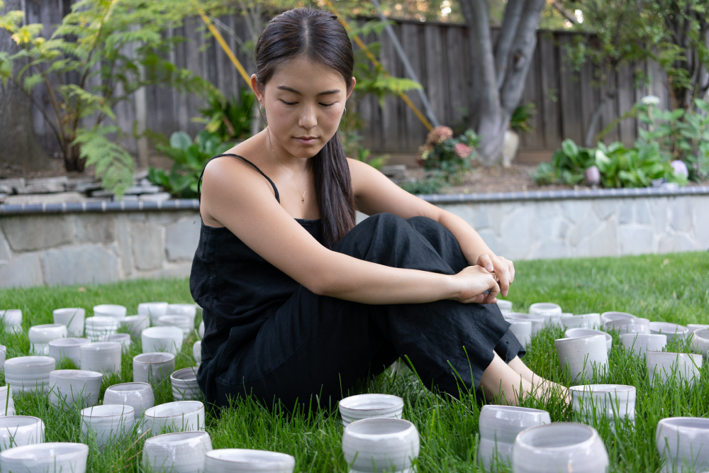 Janice Suhji sitting on grass surrounded by her ceramic tumblers.