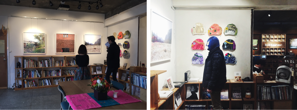 Two images, on the left, two people are looking at Janice's art hung on the wall of a gallery. The right, shows a person with a luchador mask on with Janice's masks in the background.